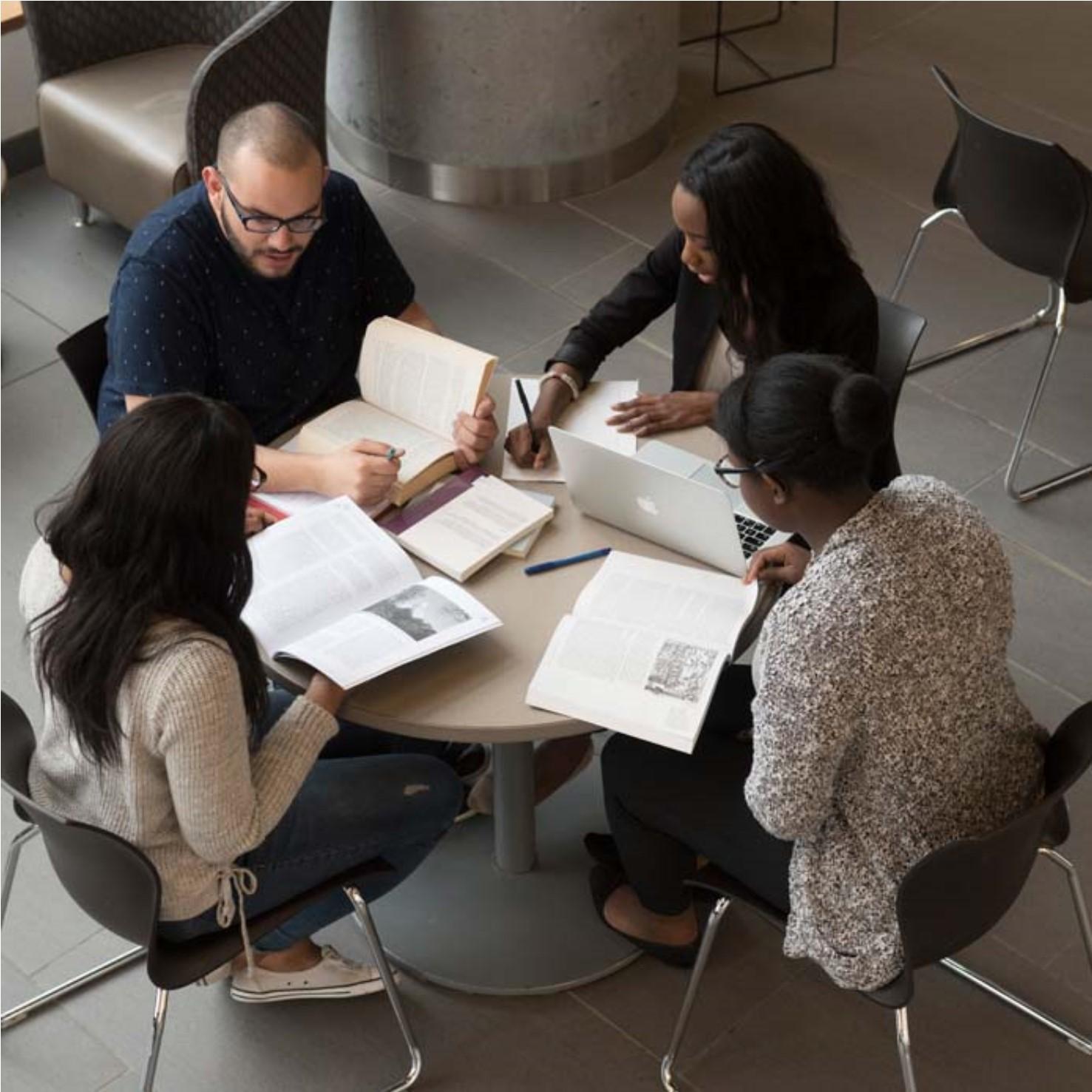 Quatre étudiants autour d'une table couverte de livres